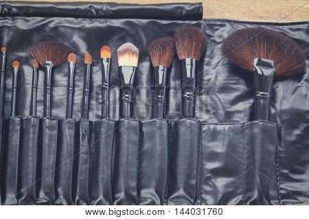 black make up brushes in leather pocket, retro toned