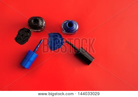 Two bottles of nail polish displayed on a red background. Top view.