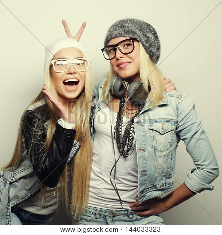 lifestyle portrait of two pretty teen girlfriends smiling and having fun, wearing hipster clothes and hats, positive mood.