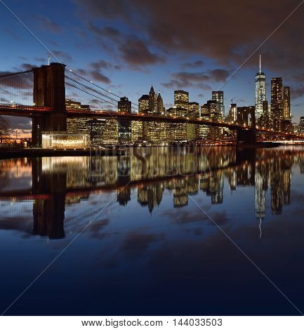 Manhattan skyline with Brooklyn Bridge reflected in the waters of the East River.