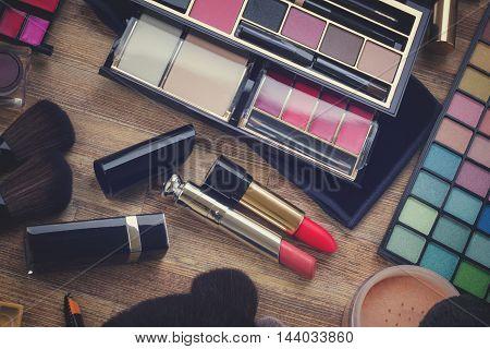 set of brushes, lipsticks, maskara, eye shadows and powder on wood, retro toned