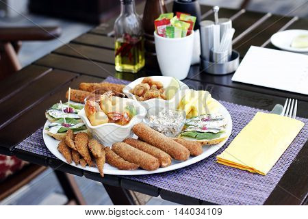 Nibbles sharer plate. King Prawns, Baby shrimps in bread crumbs, anchovies on toast bread , fish fingers, crab sticks in bread crumbs, sardines in bread crumbs