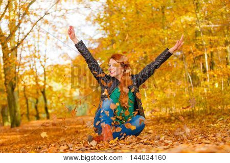 Relax leisure outdoor nature woodland concept. Cheerful ginger woman in park. Young redhead lady having fun with leaves tossing foliage around.