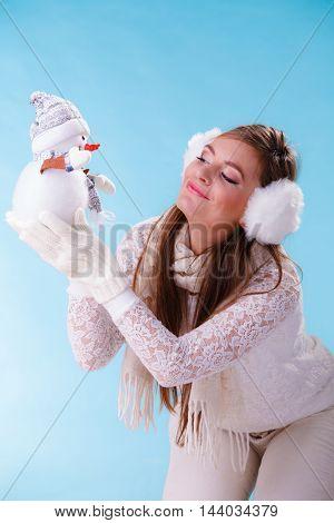 Pretty cute woman holding little snowman. Attractive girl in studio on blue. Winter.
