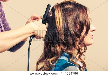 Stylist curling hair for young woman. Girl care about her hairstyle