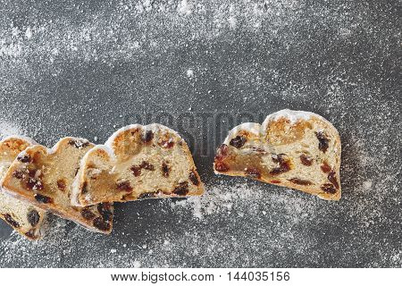 Christmas stollen. Sliced Christmas stollen with icing sugar. Top view, vintage toned image, blank space.