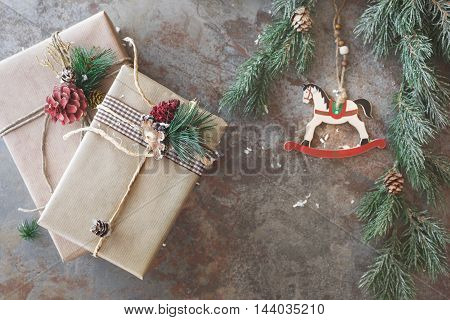 Christmas background. Two Christmas gifts and  ornament on rustic board. Top view, vintage toned image, blank space