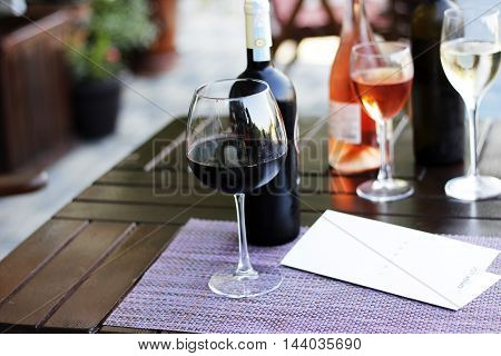 Wine collection. Wine bottles, high wineglasses and restaurant menu drink list on the napkin and wood table.