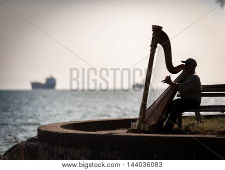 Vancouver Canada - June 262009 : Musician harpist performer silhouette sit on a bench near the sea in Vancouver Canada