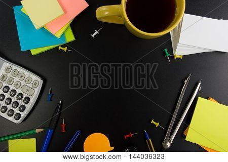 Office table desk top view with set of colorful supplies, cup, pen, pencils, flower, notes, cards on black board desk table background. Top view and copy space for ad text.