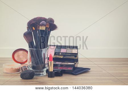 can with brushes and make up products on wooden table with copy space, retro toned