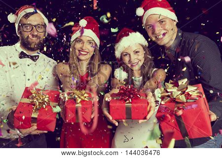 Two beautiful young couples having fun at New Year's Eve Party holding wrapped presents ready for exchange at midnight