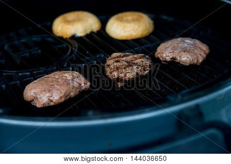 Roasting delicious hamburger patties on a metal grill