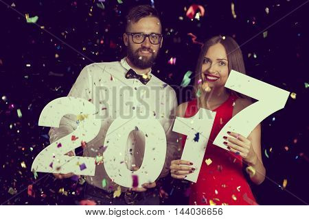 Young couple in love having fun at New Year's Eve party holding cardboard numbers 2017