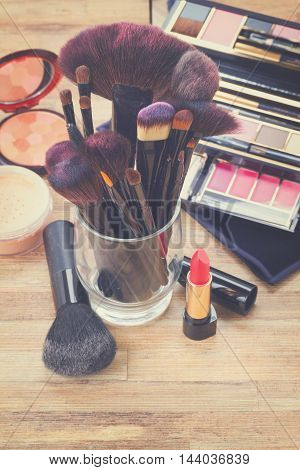 glass with brushes and make up products on wooden table, retro toned