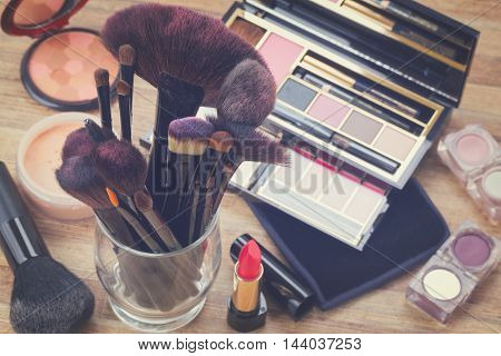 glass can with brushes and make up products on wooden table, retro toned