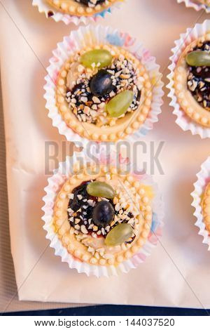 Beautiful tasty cake with grape on the table