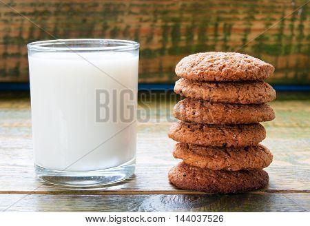 Milk In Glass Mug With Oatmeal Cookies On Wooden Table.