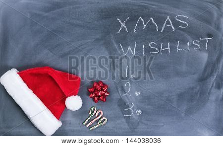 Santa cap gift bow and candy canes on erased chalkboard with Christmas wish list written on board.