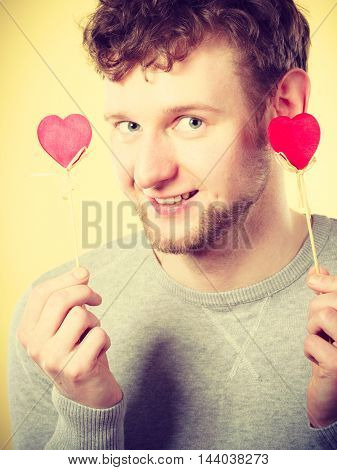 Love romance concept. Happy man holding hearts. Young smiling male holding small items on pole.