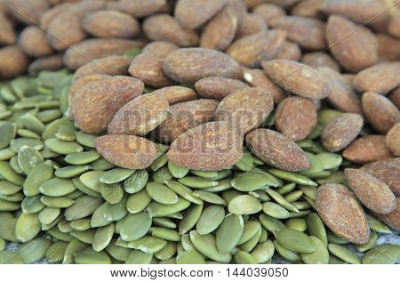 a pile of pumpkin seeds and almonds