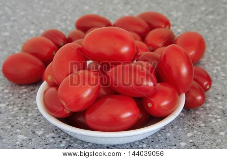 a white bowl on a table of red tomatoes