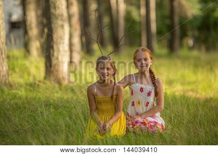 Two funny little girls pose for a photo in the park.