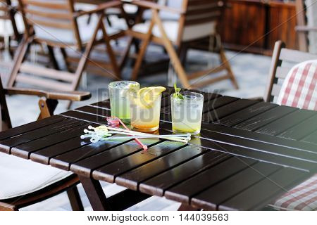 Glasses of lemonade on wood table. Three glasses of water with fresh lemon, ice, fruit, berry and mint