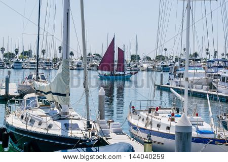Yachts Moored At Marina And Red Sails