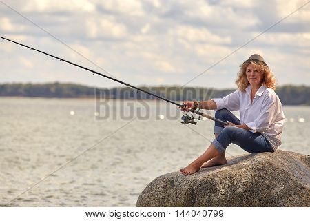 mature woman fisher sitting looking at camera