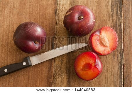 High Angle Still Life View of Trio of Plums on Rustic Wooden Table with One Sliced in Half by Sharp Knife to Reveal Inner Pit or Stone