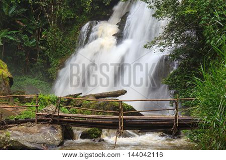Tropical rain forest landscape with jungle plants flowing water of Pha Dok Xu waterfall and bamboo bridge. Mae Klang Luang village Doi Inthanon National park Chiang Mai province Thailand