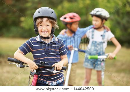 Interracial group of children with bike and scooter at the park in summer