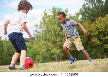 Two boys playing soccer at the park