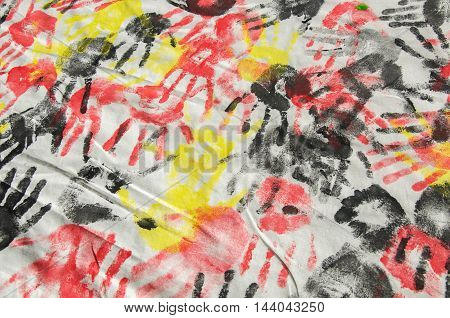 Kids arts and crafts product with red, yellow and black hand prints repeated on a cloth background.