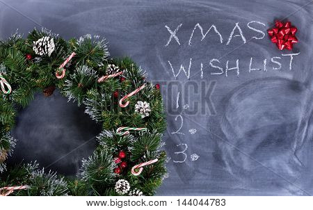 Wreath gift bow and candy canes on erased chalkboard with Christmas wish list written on board.