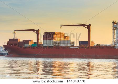 Container Cargo freight ship with working crane loading bridge in shipyard at sunrise time for Logistic Import export and oil refinery factory background
