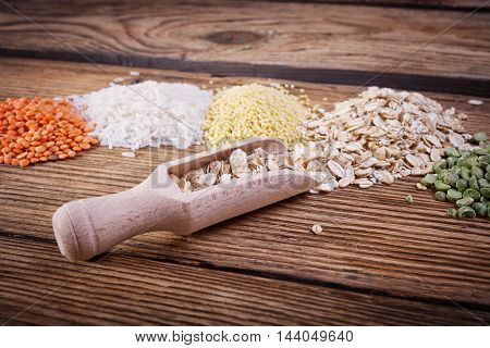 Krupa scoop, wooden spoon, an assortment of cereals, a table of old wood, the grain harvest, organic food, the texture of old wood, kitchen utensils, health food, scattering grains.