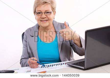 Elderly Business Woman Showing Thumbs Up And Working At Her Desk In Office, Business Concept