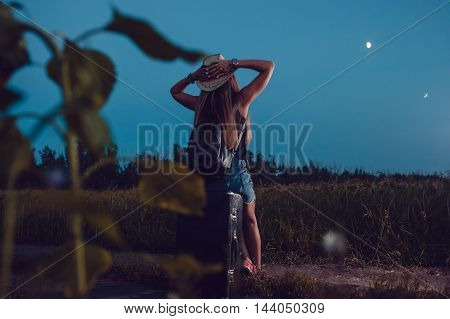 She lost in the sunflower field sits on a suitcase. Waiting for help. Night.