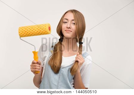 Girl with a paint roller for DIY painting.
