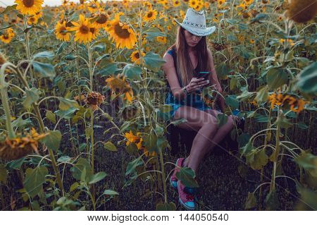 Girl in a cowboy hat lost in sunflower field catches a cellular phone. Sunset.