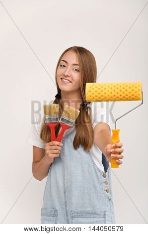 Girl with a paint brush and paint roller. Tools for DIY repair and painting.