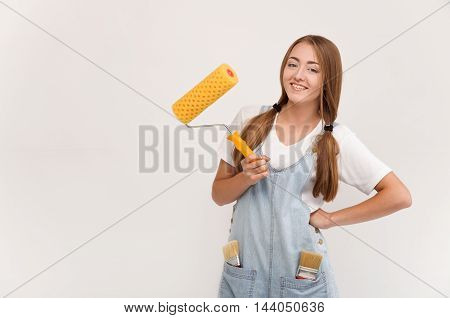 woman holding a paint roller. tools for DIY repair and painting