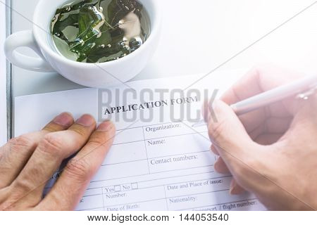 teacup and hand with pen over application form