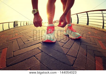 young woman runner tying shoelaces on city road