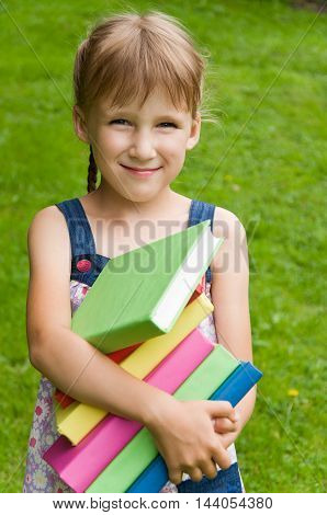 little schoolgirl holding a book in her hands and smiling