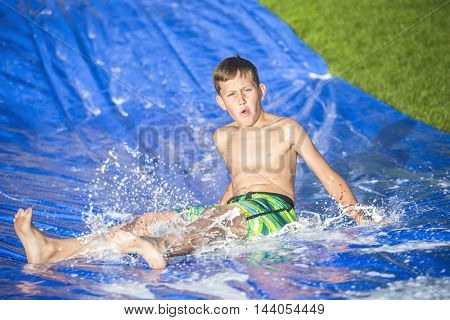 Teen boy sliding down a slip and slide outdoors