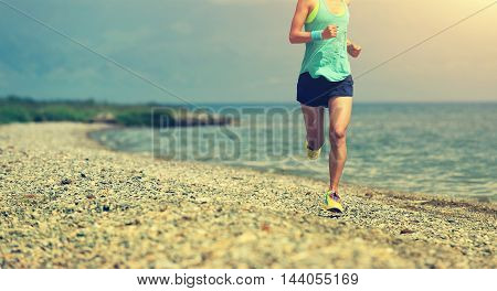 healthy young woman trail runner running on seaside