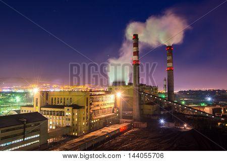 Coal powered plant and smoke stacks at night